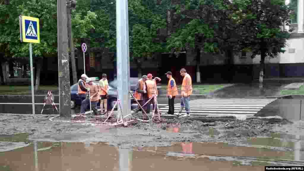 За кілька сот метрів від стадіону робітники вкладають бордюрний камінь (фото О. Овчинникова)