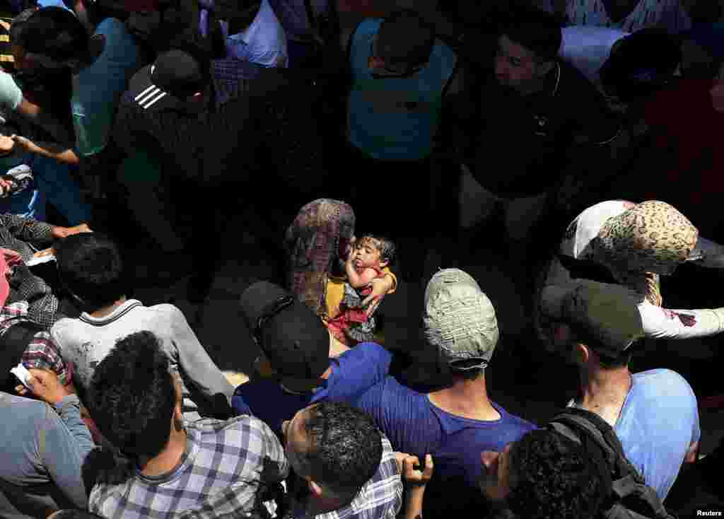 Syrian men form a safety passage for refugee women following clashes during a registration procedure in the national stadium on the Greek island of Kos. Local authorities are struggling to cope with the increasing numbers of migrants and refugees arriving on dinghies from the nearby Turkish coast. (Reuters/ Yannis Behrakis)