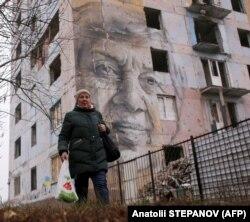 Учительница украинского языка Марина Марченко проходит возле поврежденного обстрелами дома в прифронтовой Авдеевке, на котором нарисован ее портрет. Авдеевка, 28 ноября 2019 года
