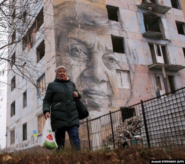 Вчителька української мови Марина Марченко проходить біля пошкодженого обстрілами будинку в прифронтовій Авдіївці, на якому намальований її портрет. Авдіївка, 28 листопада 2019 року