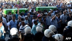 People shout slogans while they carry coffins of victims of a suicide bombing that killed at least 31 people in the town of Suruc near the border with Syria on July 20.