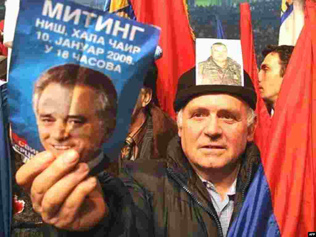 A supporter of Serbian Radical Party carries pictures of his party leader Tomislav Nikolic (L) and Bosnian Serb army commander and most wanted war crimes fugitive General Ratko Mladic (R) during a pre-election rally in Nis, 10 January 2008.
