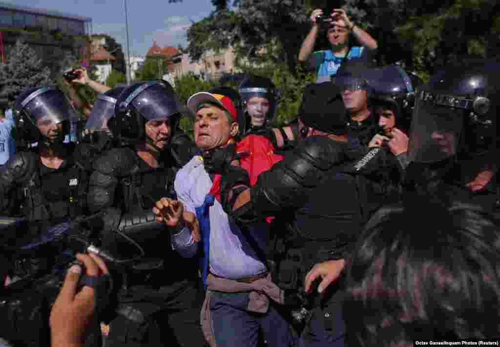 Police officers hold a man as thousands of Romanians hold rallies in major cities across the country and outside government headquarters in the capital, Bucharest, on August 10. (Reuters)