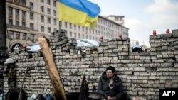 Участник антиправительственного протеста сидит у баррикады в центре Киева. 24 февраля 2014 года.
