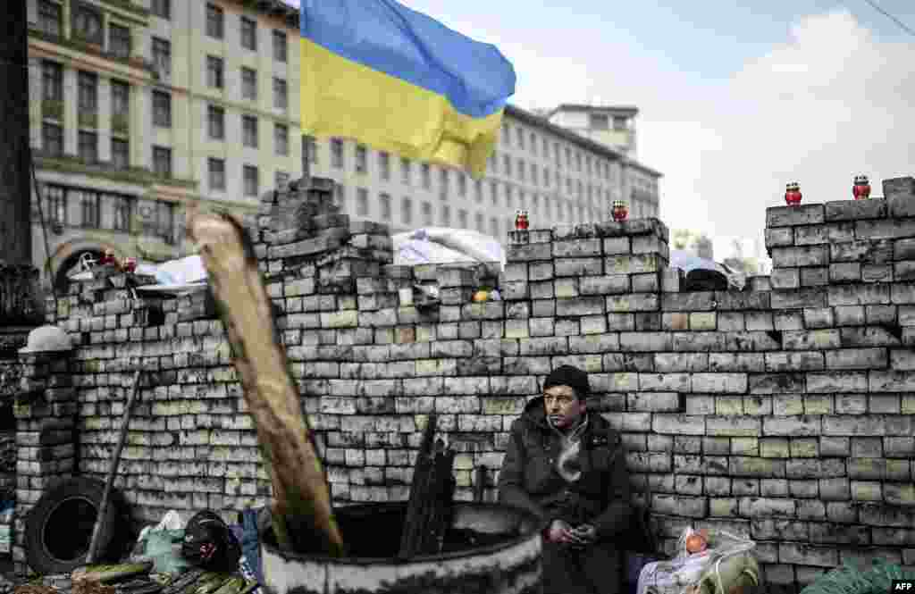 An antigovernment protestor sits behind a barricade on Kiev's Independence Square. (AFP/Bulent Kiric)