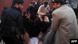 Пакистанские полицейские уносят мертвое тело своего коллеги. Иллюстративное фото. Пешавар, 24 февраля 2012 года.