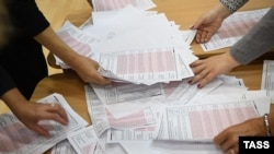 Members of a local election commission count ballots at a polling station following municipal elections in Yekaterinburg on September 10.