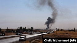 Smoke rises as Kurdish security forces withdraw from a checkpoint in Alton Kupri, on the outskirts of Irbil, on October 20.