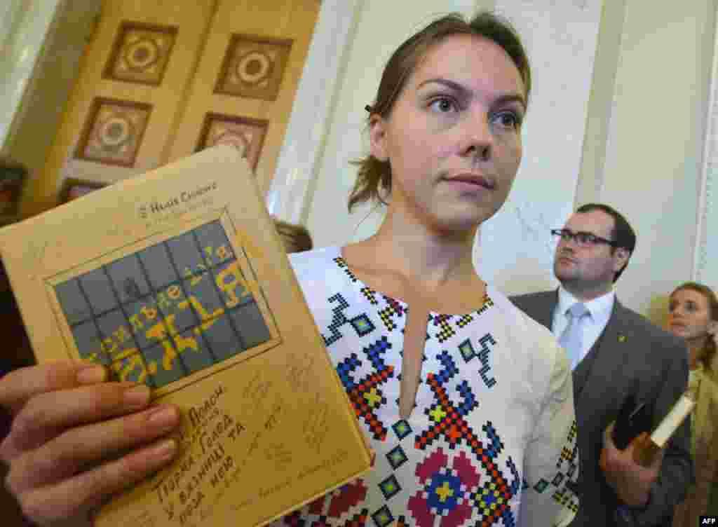 Віра Савченко тримає книгу своєї сестри «Сильне ім'я Надія» на презентації у Верховній Раді. 16 вересня 2015 року