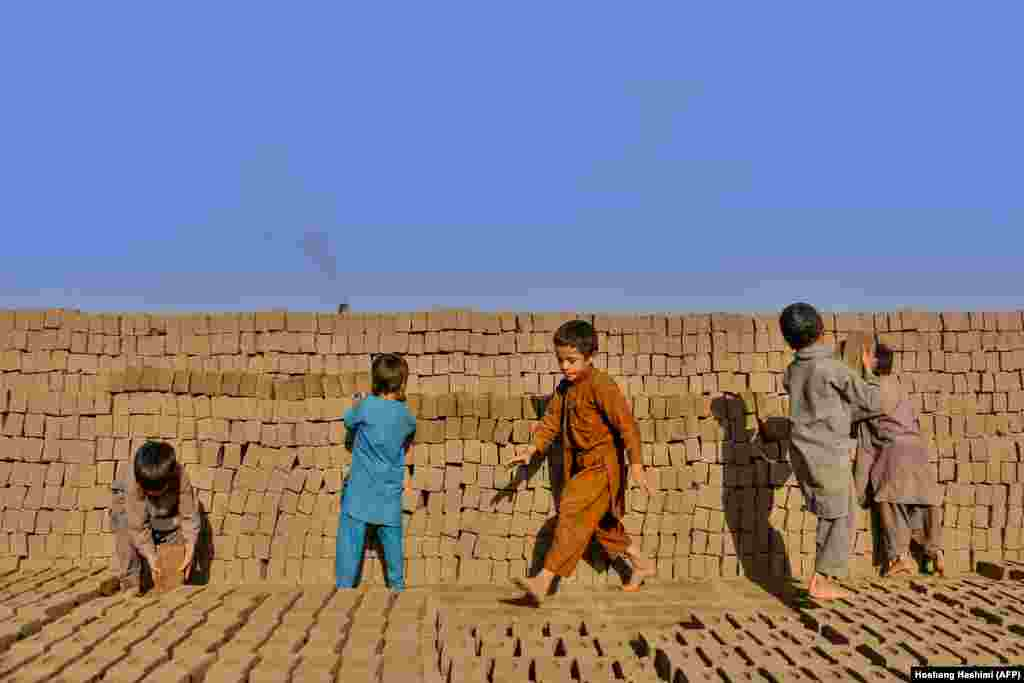 Young children stack bricks as they work as labourers at a factory on the outskirts of Herat, Afghanistan. (AFP/Hoshang Hashimi)