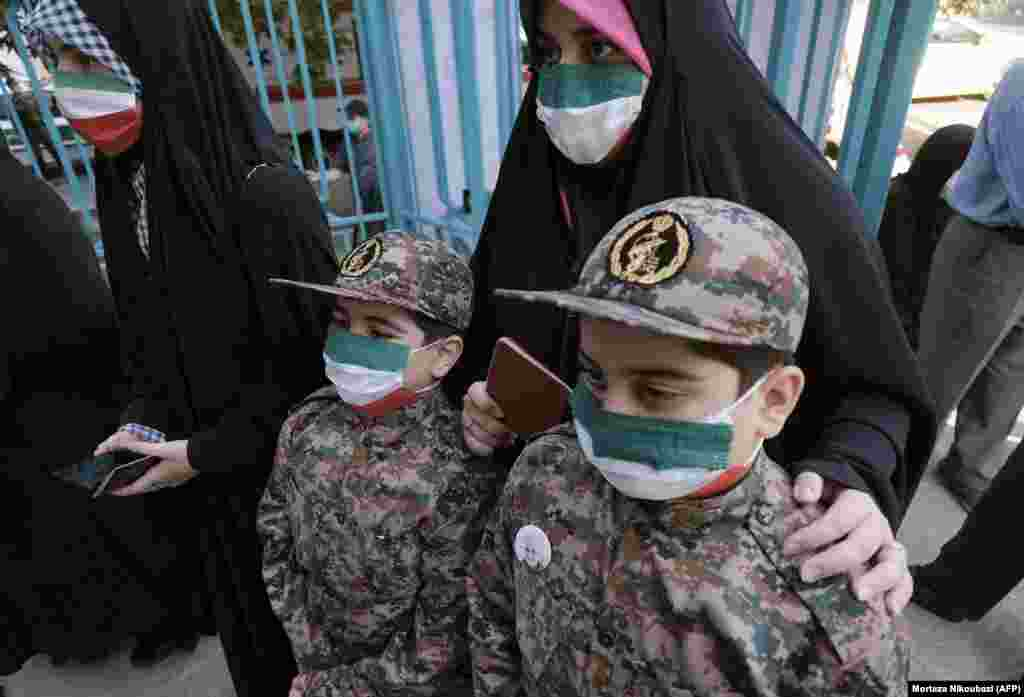 An Iranian mother and her children, wearing Islamic Revolutionary Guards Corps uniforms, line up at a polling station to cast her vote for the presidential election on June 18.
