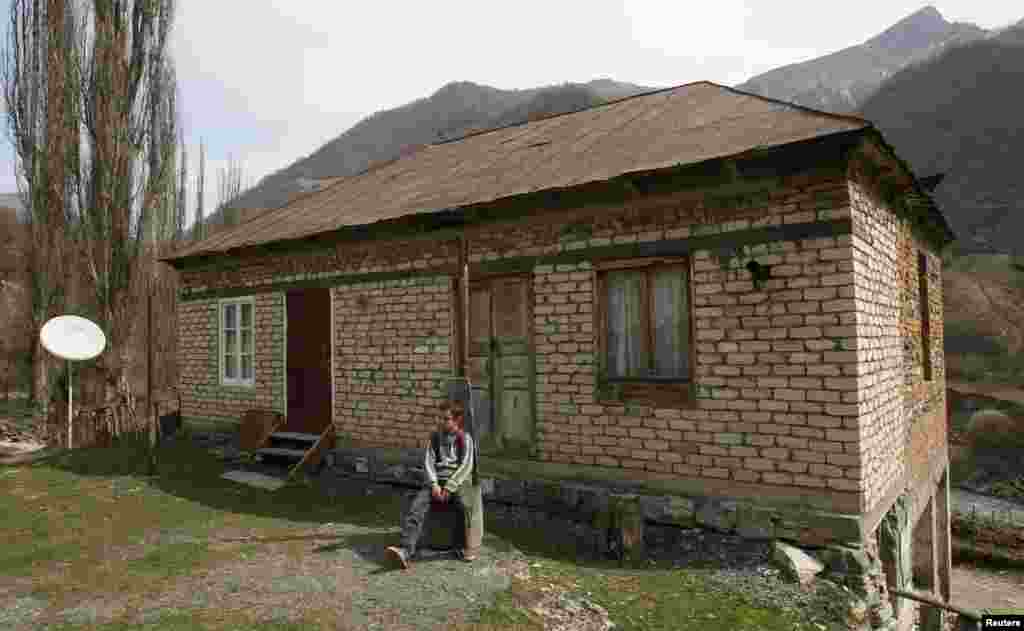 Bacho waits for his teacher in front of the house that functions as his school.