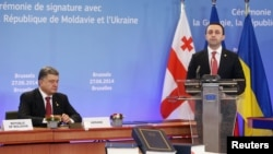 Премьер-министр Грузии Ираклий Гарибашвили выступает после президента Украины Петра Порошенко во время церемонии подписания соглашения о сотрудничестве с Евросоюзом. Брюссель. 27 июня 2014 года.