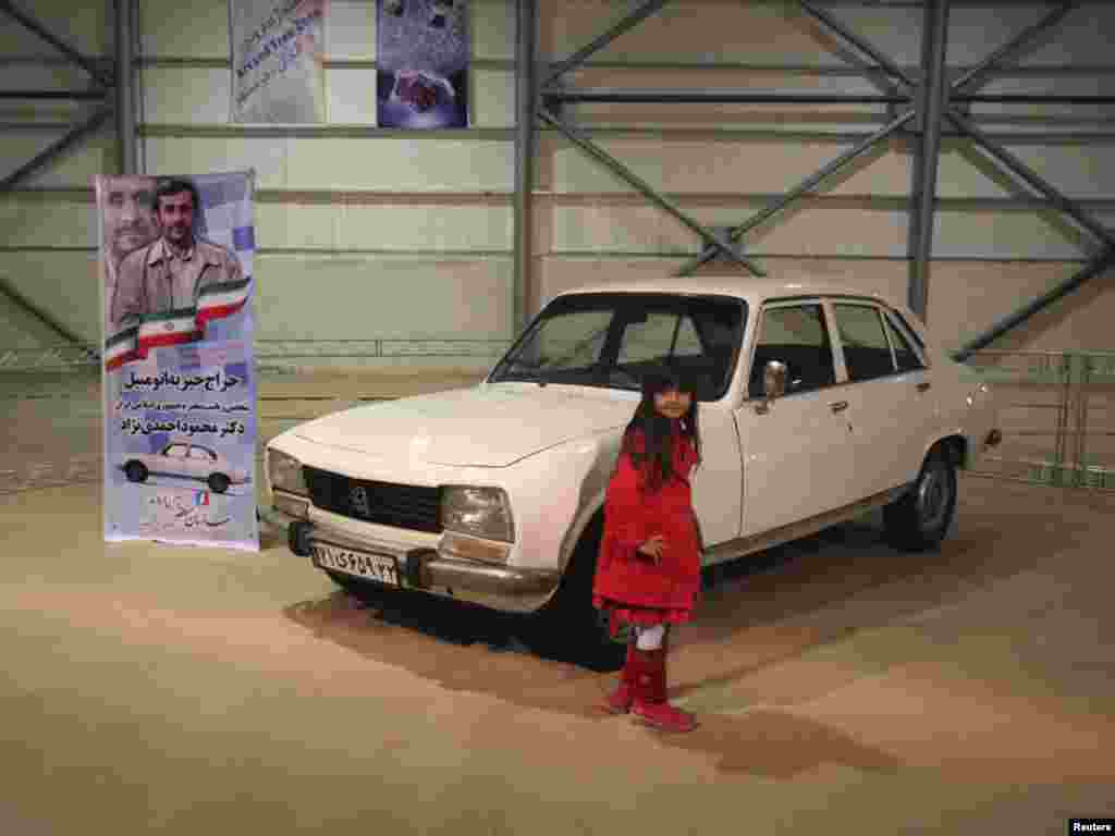 A girl poses next to Iran President Mahmud Ahmadinejad's 1977 Peugeot 504, which was auctioned for charity. Photo by Mohammadreza Dehdari for Reuters