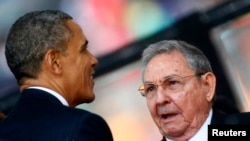 Барак Обама менен Рауль Кастро Түштүк Африканын мурдагы президенти Нельсон Манделанын тажиясында кол алышкан. 10-декабрь, 2013-жыл.