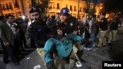 Policët duke e bartur një person të plagosur nga eksplodimi në Lahore të Pakistanit