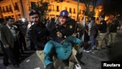 A policeman carries one of the injured after a blast in Lahore on February 13.