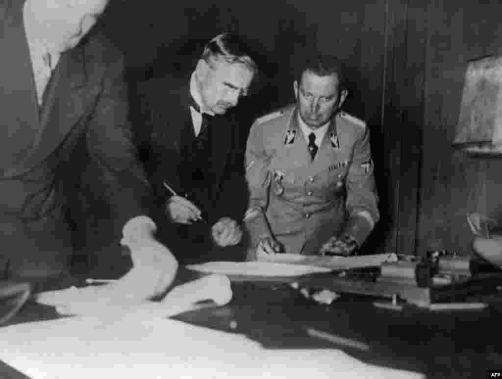U.K. Prime Minister Arthur Neville Chamberlain (left) signs the Munich Agreement as Hitler's secretary, Martin Bormann, looks on in Munich in the early hours of September 30, 1938 (although the document was dated September 29).