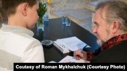 Сашко Лірник підписує свої книжки після виступу в Празі