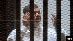 Ousted Egyptian President Muhammad Morsi gestures in a cage during a court hearing in Cairo in 2015.