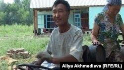 Житель села Еркин Кайдарбек с женой Кульзирой на тракторе. Село Коктума Алматинской области, 13 июля 2012 года.