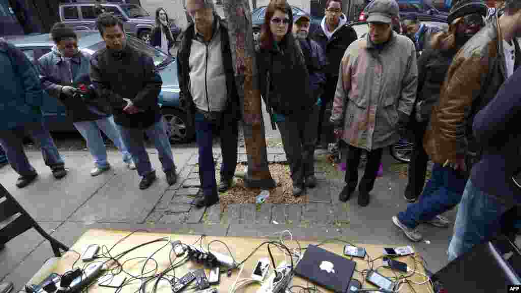 People wait to have mobile phones and laptops charged from a generator set up in the West Village as New Yorkers coped with the aftermath of Hurricane Sandy. The storm left large parts of New York without power. (AFP/Timothy A. Clary)