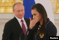 """Pole vaulter Yelena Isinbayeva and Russian President Vladimir Putin during his send-off for the Russian Olympic team at the Kremlin in 2016. A day after calling homosexuality a """"problem"""" in 2013, Isinbayeva said she had been misunderstood."""