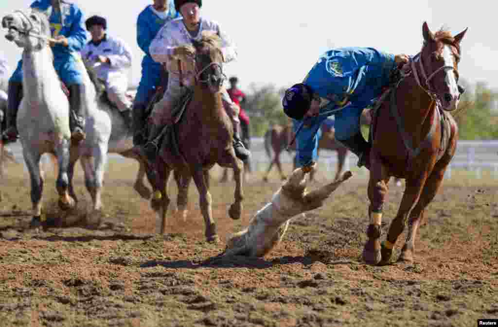 A Kazakh team member drags the goat during the match against Russia.