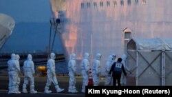 Медики и полиция в защитных костюмах поднимаются на борт Diamond Princess. 5 февраля 2020 года