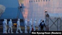 Policajci u zaštitnoj opremi ulaze na kruzer Diamond Princess(Dajmond Princez) kako bi prebacili pacijenta u bolnicu nakon što je brod stigao na terminal Daikoku u Jokohami, Japan, 7.februar 2020.