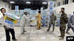 Afghan election commission workers move ballot boxes to a truck for delivery to Kabul for an audit of the presidential run-off votes in Herat province, July 17, 2014.