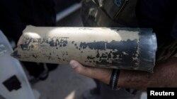 Израильский полицейский показывает остатки ракеты, запущенной в поселение Нирим с территории сектора Газа. 7 июля 2014 года.