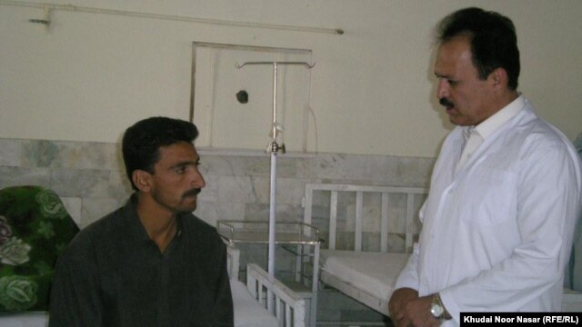 Dr. Ghulam Rasool (right) speaks to a patient.