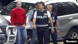 Police escort Anders Behring Breivik (left) back to Utoeya island on August 13.