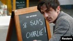 """Адель Дефилю, мусульманин, родившийся во Франции, сидит рядом с рекламным щитом с надписью: """"Шарли - это я"""" - у своего кафе. Лондон, 14 января 2015 года."""