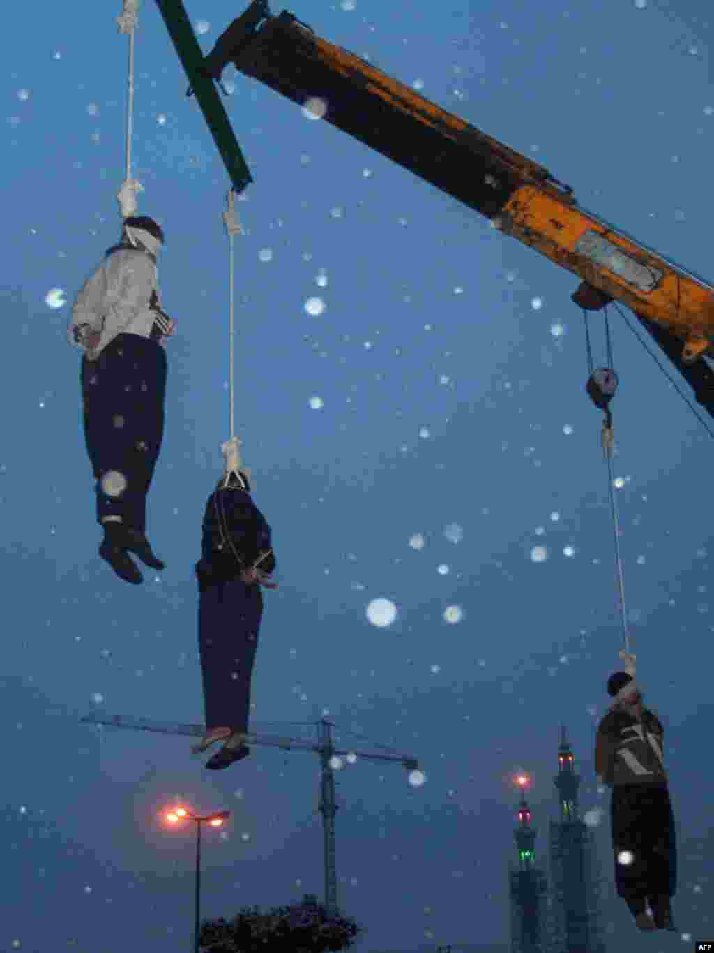 Three Iranian drug traffickers being hanged in the central city of Qom - Three Iranian drug traffickers hang limply from the nooses as it snows in a square in the central city of Qom, south of Tehran, on January 2. Iran hanged 13 convicted criminals that day, including the mother of two young children who had been found guilty of murdering her husband after discovering he was having an affair.