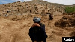 Afghan survivors mourn for their relatives at the site of a landslide at the Argo district in Badakhshan Province.