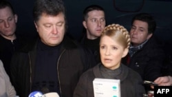 Prime Minister Yulia Tymoshenko (right) holds up packs of the Tamiflu antiviral medicine.