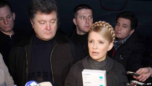 Prime Minister Yulia Tymoshenko (right) holds up packs of the Tamiflu antiviral medicine.
