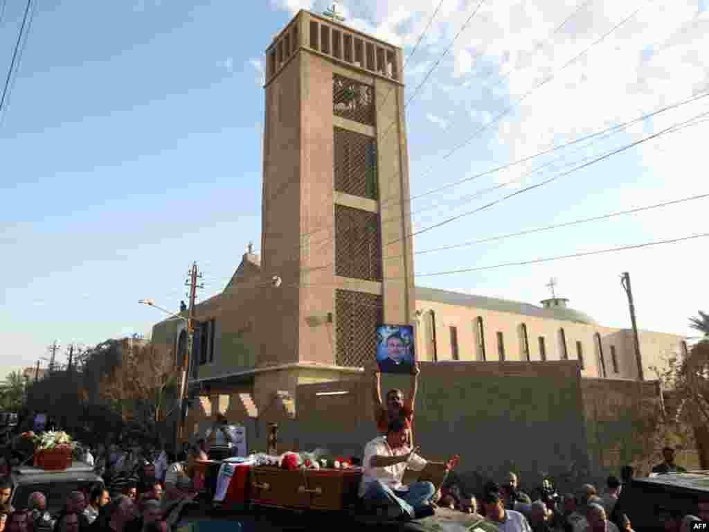 تصویر کشیش ۳۲ سالهای که در جریان گروگانگیری کلیسا بغداد کشته شد در دست عزاداران در بغداد- ۱۱ آبان - IRAQ, Baghdad : Iraqi mourner holds up a portrait of 32-year-old slain priest Taher Saadallah Boutros, known as Father Athir (R), during a funeral procession in Baghdad on November 2, 2010 for the victims of the Syrian Catholic cathedral carnage in which more than 40 Christians, including two priests, were killed on October 31 during a hostage drama with Al-Qaeda gunmen. AFP PHOTO/AHMAD AL-RUBAYE