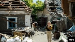 A local woman stands next to her shell-damaged house in Ukraine's Donbas region. (file photo)