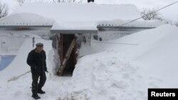 Мужчина стоит у своего дома, заваленного снегом. Иллюстративное фото.