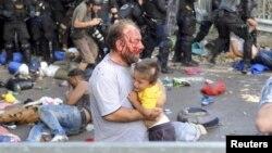 Раненый во время столкновений беженец в сербском лагере мигрантов Рётцке, 16 сентября 2015 года