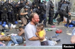 An injured migrant carries a child during clashes with Hungarian riot police at the border crossing with Serbia in Roszke on September 16.