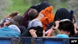 Сирийские беженцы прячут лица у границы Турции с Сирией, 15 марта 2012