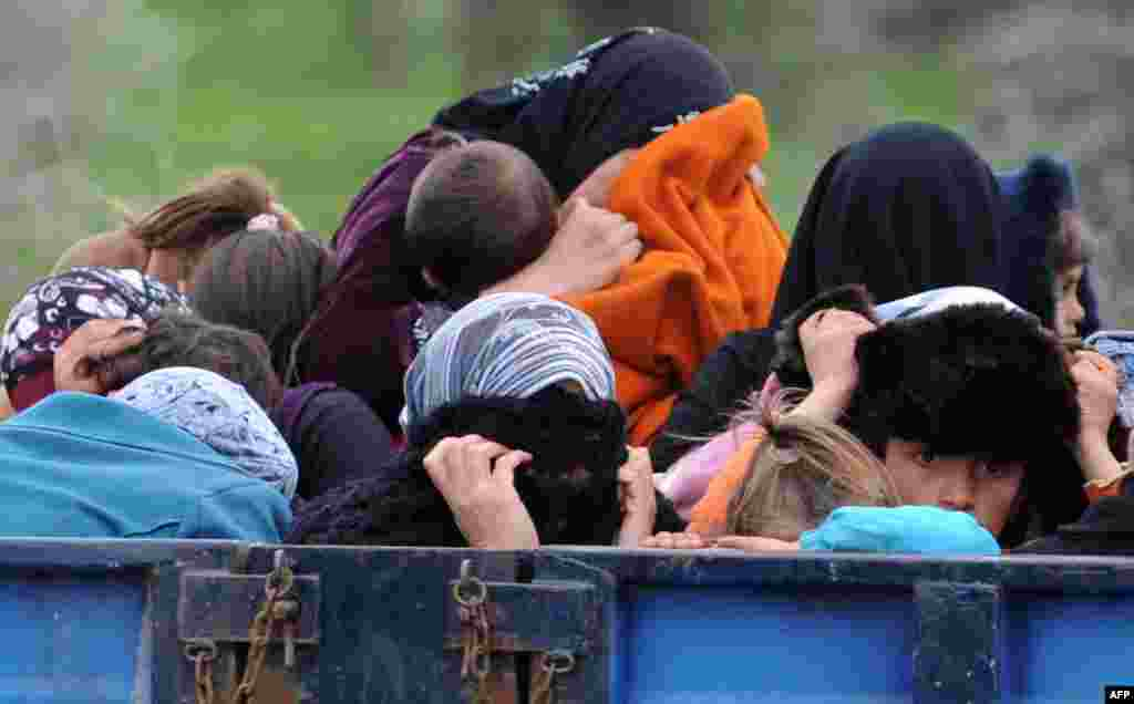 Syrian refugees hide their faces as they arrive near the border between Syria and Turkey at Reyhanli in Antakya. (AFP)