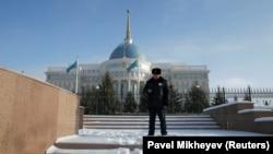 Сотрудник полиции на фоне здания администрации президента Казахстана.