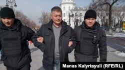 Полицейские ведут задержанного в Алматы.