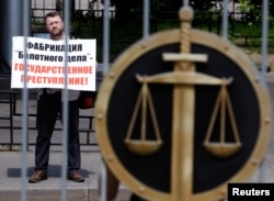 """Мужчины у здания суда в Москве проводит акцию в поддержку подсудимых по """"Болотному делу"""". 6 июня 2013 года. Иллюстративное фото."""