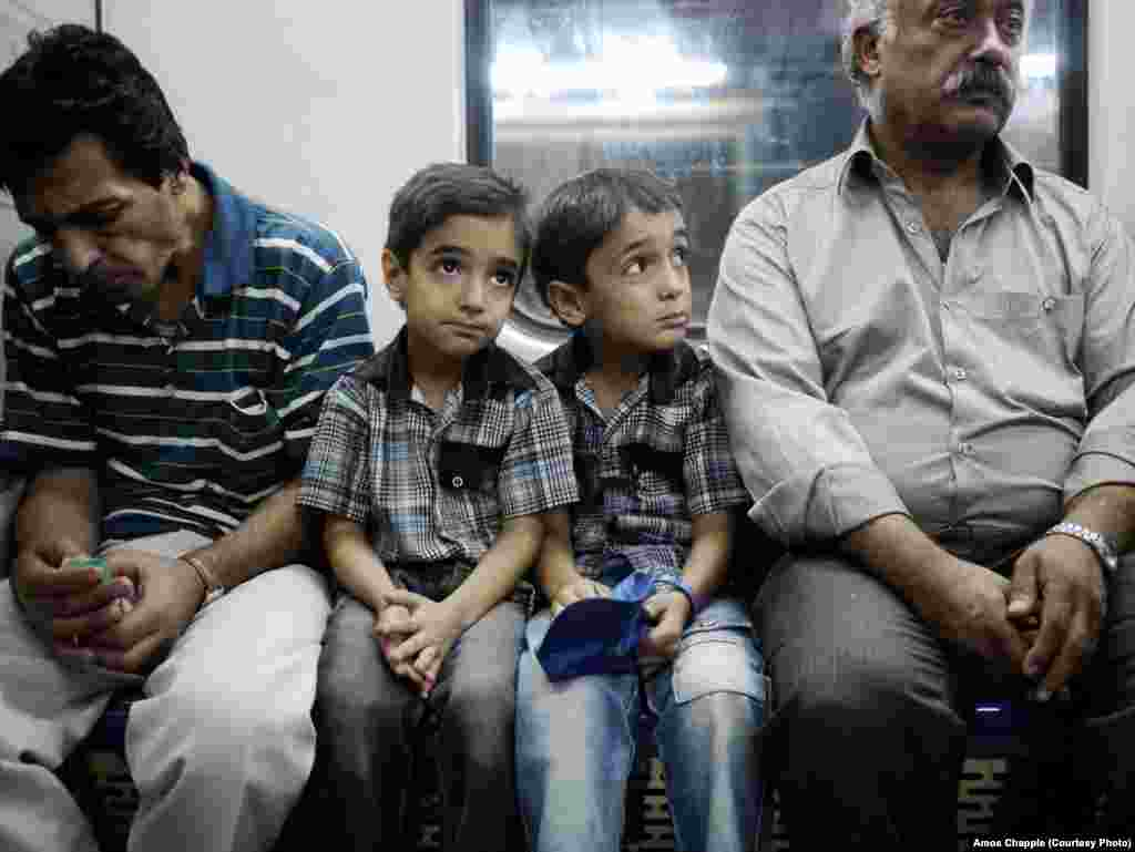 Young twins ride on the Tehran Metro.